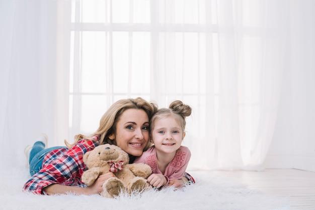 Portrait, de, mère fille, mensonge, sur, fourrure, tenue, nounours Photo gratuit