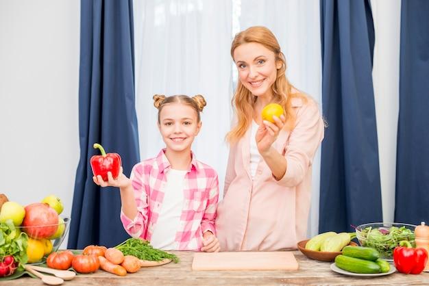 Portrait, de, mère fille, tenue, citron jaune, et, poivron rouge, dans main, regarder appareil-photo Photo gratuit