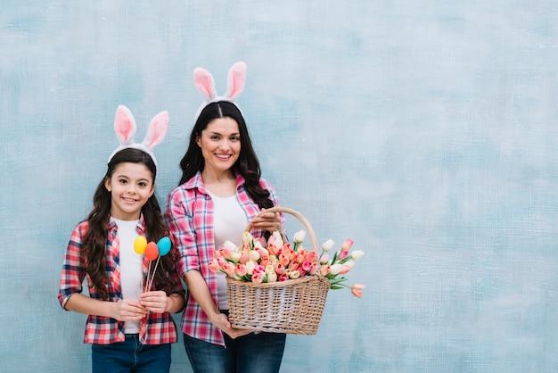 Portrait, de, mère fille, tenue, panier, de, tulipes, et, oeufs pâques, contre, toile de fond bleu Photo gratuit
