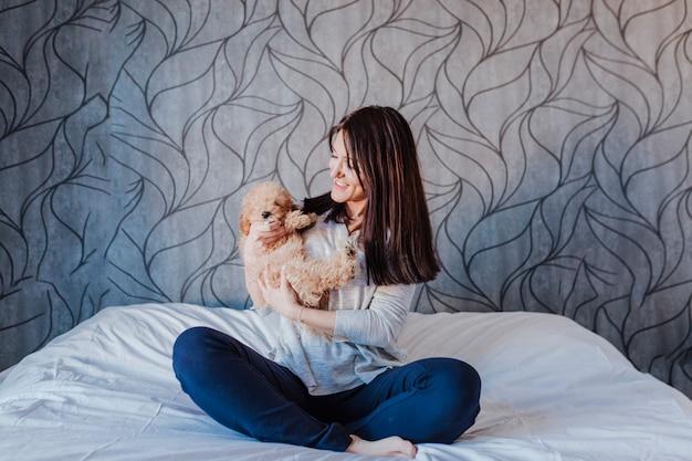 Portrait D'un Mignon Caniche Brun Avec Sa Jeune Femme Propriétaire à La Maison, De Jour, à L'intérieur. Photo Premium