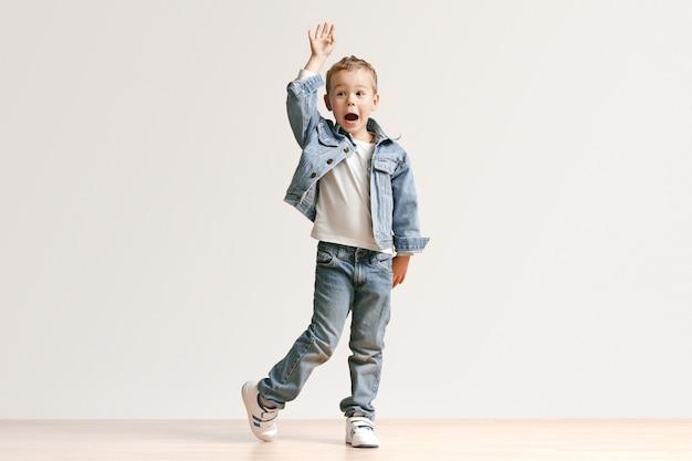 Le Portrait De Mignon Petit Garçon Enfant Dans Des Vêtements De Jeans élégants Regardant La Caméra Contre Le Mur Blanc Du Studio. Concept De Mode Pour Enfants Photo gratuit