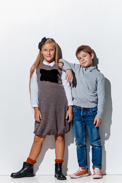 Le Portrait De Mignon Petit Garçon Et Fille Dans Des Vêtements De Jeans élégants Regardant La Caméra Au Studio Photo gratuit