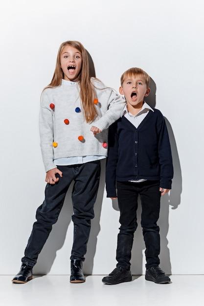 Le Portrait De Mignon Petit Garçon Et Fille En Vêtements Jeans élégants Posant Photo gratuit