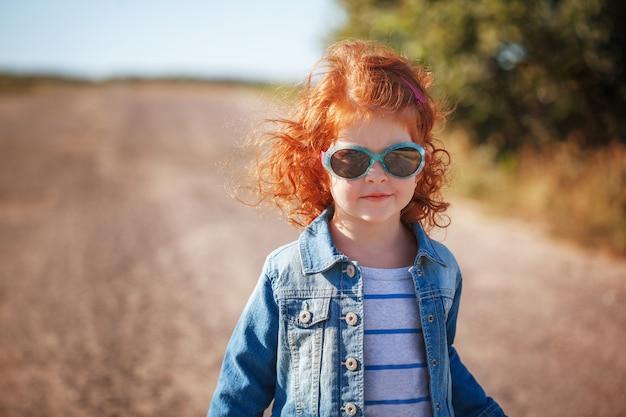 Portrait mignonne petite fille frisée rouge à lunettes de soleil en journée ensoleillée Photo Premium