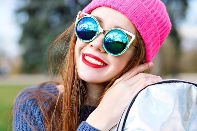Portrait De Mode Positif En Plein Air De Superbe Belle Femme Au Gingembre, Posant Au Parc De La Ville, Portant Un Chapeau Hipster Et La Météo, Des Lunettes De Soleil De Luxe à La Mode, Des Jeunes, Des Vacances, Des Lèvres Rouges, Des Couleurs Pastel. Photo gratuit