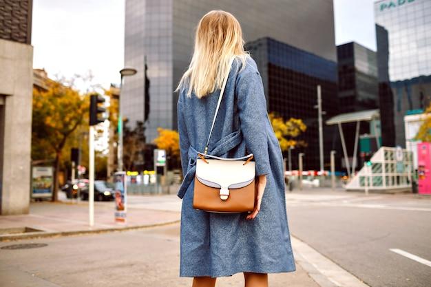 Portrait De Mode De Rue De Femme Blonde Portant Un Manteau Bleu Et Un Sac élégant, Posant En Arrière, Touriste De New York, Saison Froide Printemps Automne. Photo gratuit