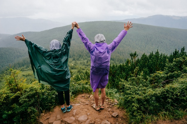 Portrait de mode de vie de derrière de heureux couple de voyager amoureux en imperméables se tenir au sommet de la montagne en jour d'été pluvieux Photo Premium