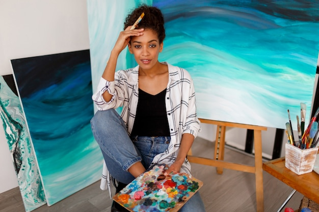 Portrait De Mode De Vie De Jeune étudiant Africain Assis Avec Des Illustrations Dessinées à La Main En Acrylique Abstrait Mer Au Studio. Photo gratuit