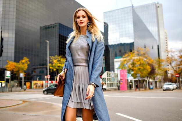 Portrait De Mode De Vie En Plein Air De Jolie Jeune Femme D'affaires Blonde, Marchant Dans La Zone De Bâtiments Modernes, Vêtu D'un Manteau Bleu Et D'une Robe Grise Féminine. Photo gratuit