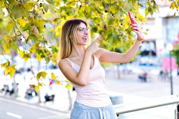 Portrait De Mode De Vie De Printemps De Jolie Femme Blonde Faisant Selfie Et Parlant En Chat Vidéo Avec Son Amie, Vêtements Sportifs Décontractés, Couleurs Pastel Ensoleillées. Photo gratuit
