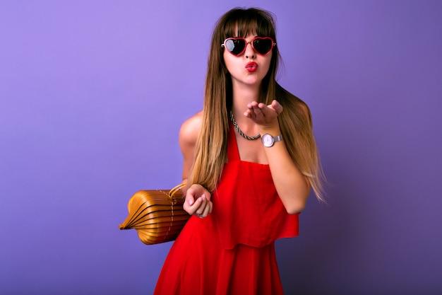 Portrait De Mode De Vie En Studio De Jolie Femme Brune à La Mode Vêtue D'une élégante Robe Rouge D'été, Lunettes De Soleil Herat, Sac En Bois, Envoi De Baiser D'air. Photo gratuit