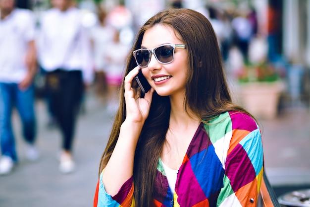 Portrait De Mode De Vie De La Ville De Jolie Femme Brune à L'aide De Téléphone Intelligent, Parlant Et Souriant, Vêtements Lumineux, Couleurs De Film Vintage. Photo gratuit