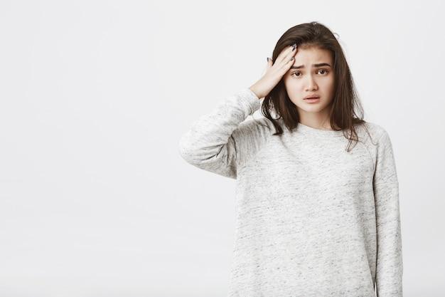 Portrait De Modèle Féminin Européen Fatigué Et Malheureux Avec Les Sourcils Froncés Et La Bouche Ouverte, Tenant La Main Sur Le Front Photo gratuit