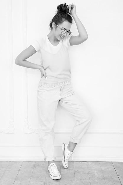 Portrait De Modèle De Jeune Fille Belle Jeune Femme Brune Avec Du Maquillage Nude Dans Des Vêtements Colorés Hipster Rose D'été En Lunettes De Soleil Posant Près Du Mur. Toute La Longueur Photo gratuit