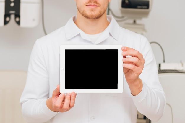 Portrait D'un Modèle De Tablette Présentant L'optométriste Masculin Photo gratuit