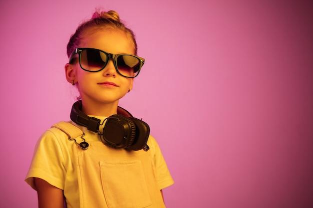 Portrait De Néon De Jeune Fille Avec Des écouteurs Appréciant La Musique. Photo gratuit