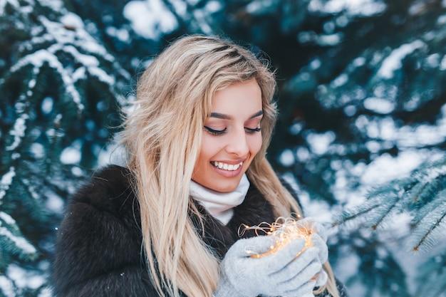 Portrait de noël de belle jeune fille en forêt d'hiver avec des lumières en plein air Photo Premium