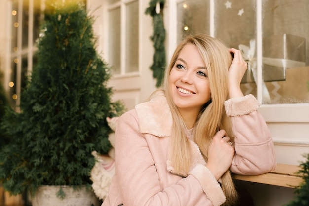 Portrait De Noël D'une Jeune Fille En Robe Rose Et Manteau En Peau De Mouton Avec Le Décor De Noël De La Maison Dans Un Intérieur élégant. Une Femme Se Prépare à Célébrer Noël Et Le Nouvel An Photo Premium