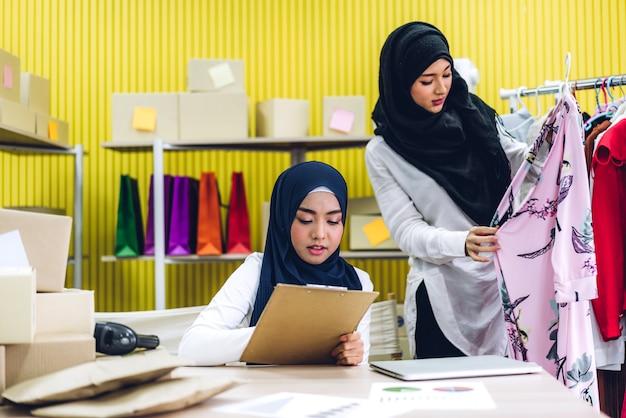Portrait Of Smiling Beautiful Two Musulman Propriétaire Femme Asiatique Pigiste Pme Business Shopping En Ligne Travaillant Sur Ordinateur Portable Avec Boîte à Colis Sur Table à La Maison - Business Expédition Et Livraison En Ligne Photo Premium