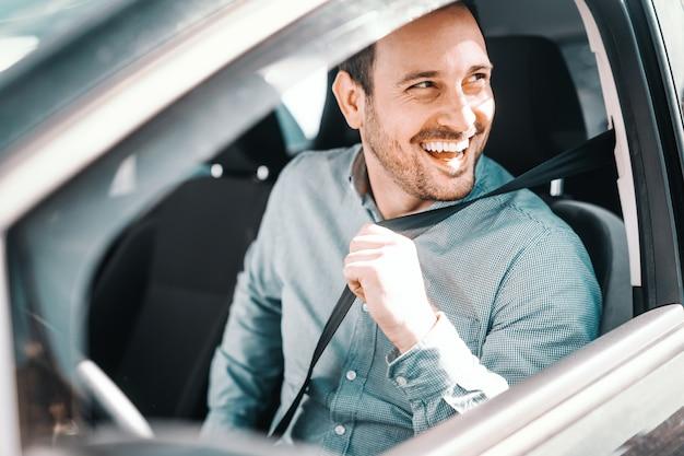 Portrait Of Smiling Caucasian Man Attacher La Ceinture De Sécurité Et Assis Dans Sa Voiture. Fenêtre Ouverte, Vue Latérale. Photo Premium