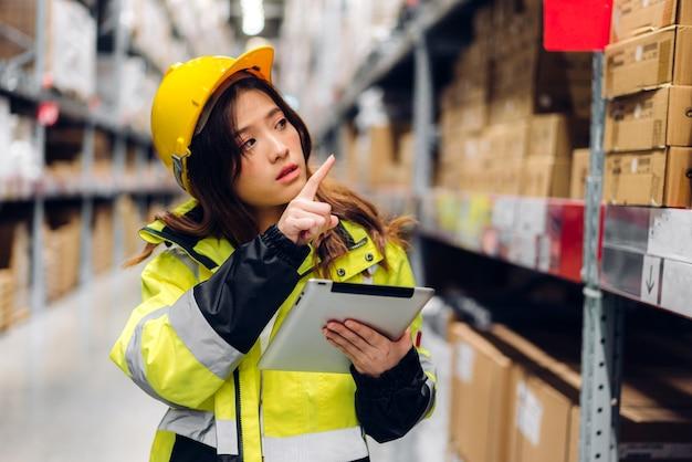 Portrait Of Smiling Ingénieur Asiatique Dans Les Casques Femme Commande Détails Sur Tablette Pour Vérifier Les Produits Et Fournitures Sur Les étagères Photo Premium