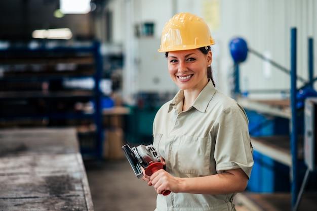 Portrait d'un ouvrier industriel avec meuleuse au travail, souriant à la caméra. Photo Premium