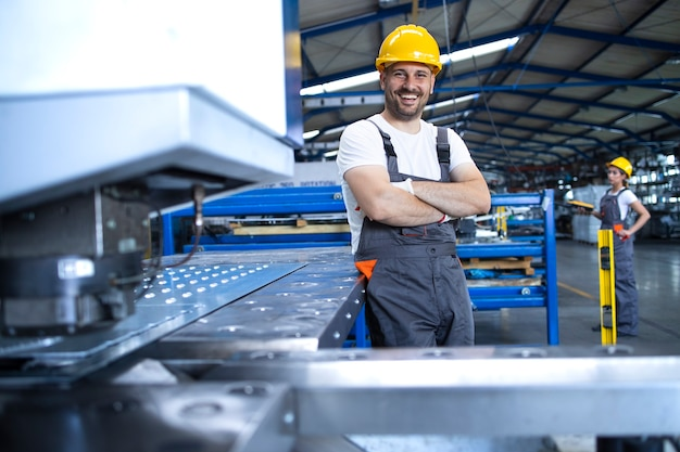 Portrait D'ouvrier D'usine En Uniforme De Protection Et Casque Debout Par Machine Industrielle à La Ligne De Production Photo gratuit