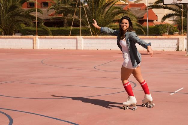 Portrait d'une patineuse tendant ses bras patiner sur un terrain en plein air Photo gratuit