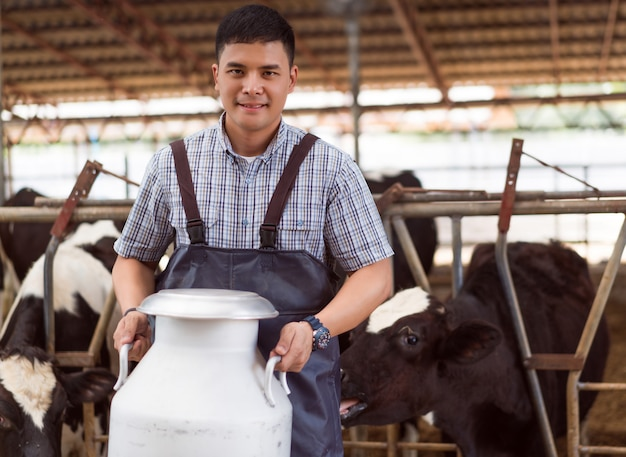 Portrait paysan asiatique tient un récipient de lait dans sa ferme. Photo Premium