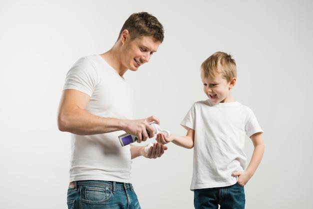 Portrait, père, pulvérisation, mousse rasage, main, fils, contre, toile de fond blanc Photo gratuit