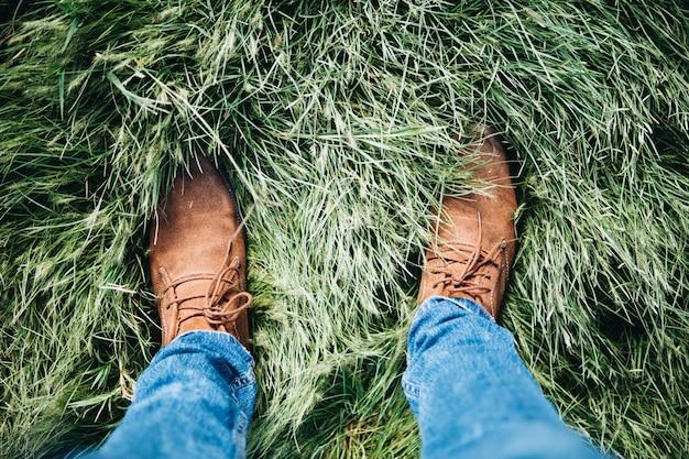 Portrait D'une Personne Portant Des Chaussures En Cuir Et Des Jeans Debout Sur Un Champ D'herbe Photo gratuit