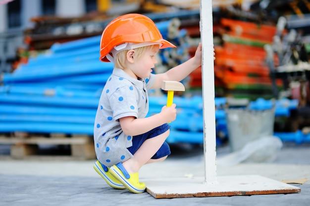 Portrait, de, petit, constructeur, dans, casques, à, marteau, travailler dehors Photo Premium