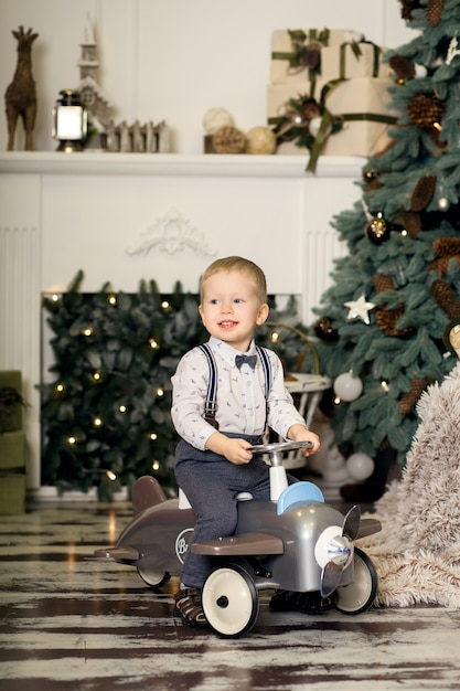 Portrait d'un petit garçon assis sur un avion jouet vintage près d'un arbre de noël Photo Premium
