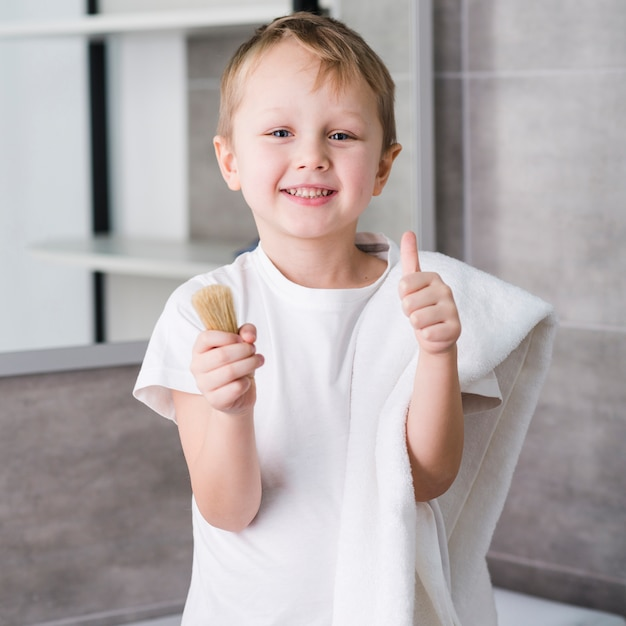Portrait d'un petit garçon heureux avec une serviette blanche sur son épaule, tenant le blaireau dans la main, montrant le pouce vers le haut de signe Photo gratuit