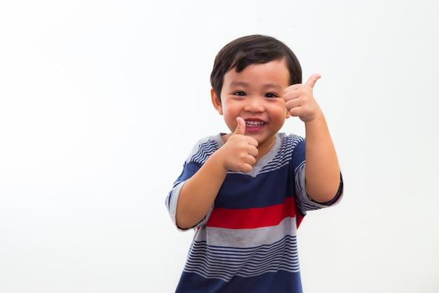 Portrait de petit garçon tient un pouce en studio Photo Premium