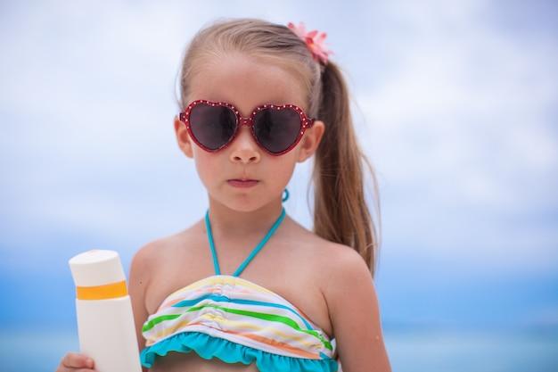 Portrait de petite fille adorable en maillot de bain détient une bouteille de lotion de bronzage Photo Premium
