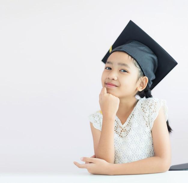 Portrait petite fille asiatique porte chapeau de diplômé et sourit avec bonheur Photo Premium