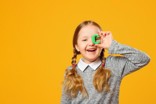 Portrait d'une petite fille. écolière tient la lettre c. Photo Premium