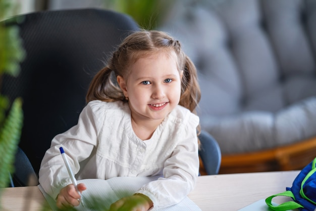 Portrait D'une Petite Fille écrivant Dans Un Cahier, étudiant à La Maison. Photo Premium
