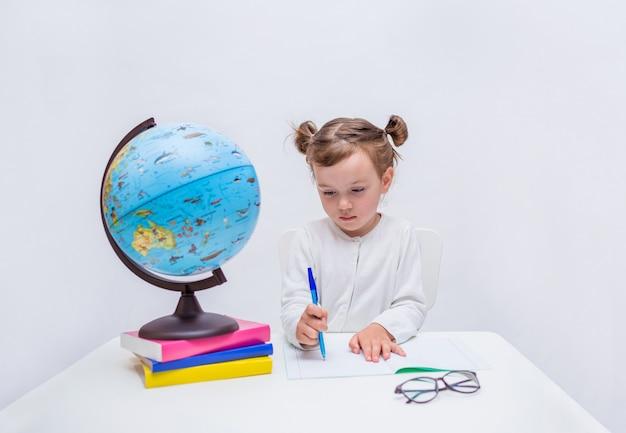 Portrait D'une Petite Fille élève écrit Avec Un Stylo Dans Un Cahier à Une Table Sur Un Blanc Isolé Photo Premium