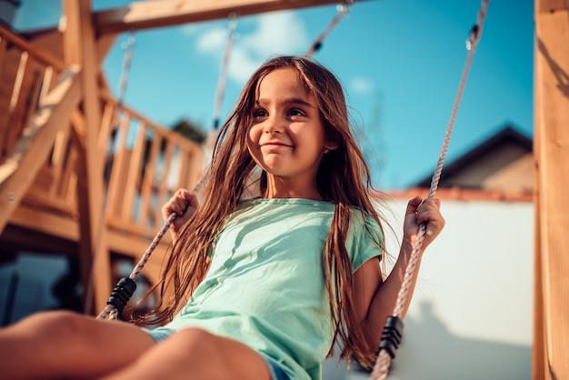 Portrait d'une petite fille heureuse assise sur une balançoire Photo Premium