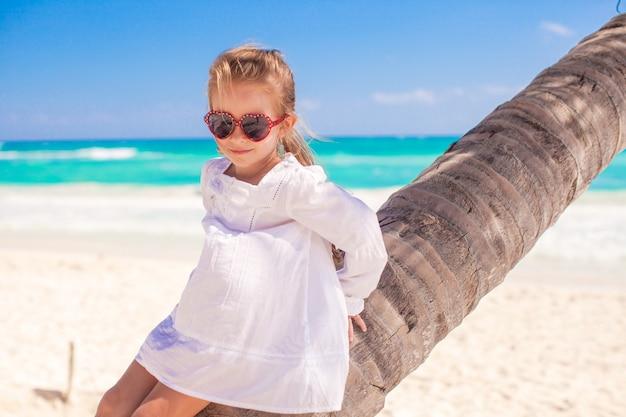 Portrait de petite fille mignonne assise sur un palmier à la plage des caraïbes parfaite Photo Premium