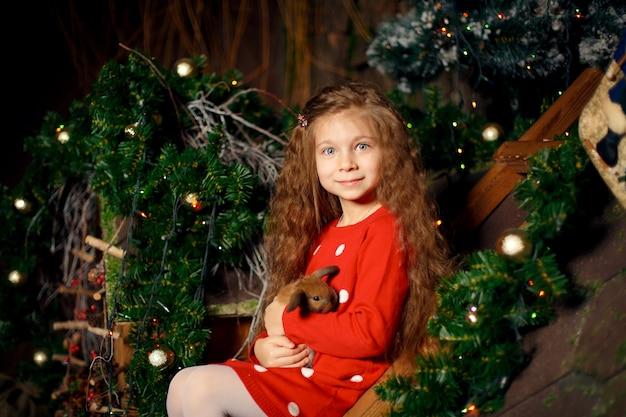 Portrait De Petite Fille Mignonne Est Titulaire D'un Lapin Dans Ses Mains. Décoration De Noel. Concept De Vacances Photo Premium