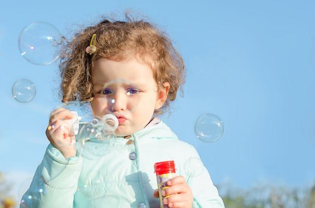 Portrait Petite Fille Mignonne Souffle Des Bulles De Savon. Enfant Heureux Joue à L'extérieur. Bébé Joue à L'extérieur Dans La Nature. Flou. Copie Espace Photo Premium
