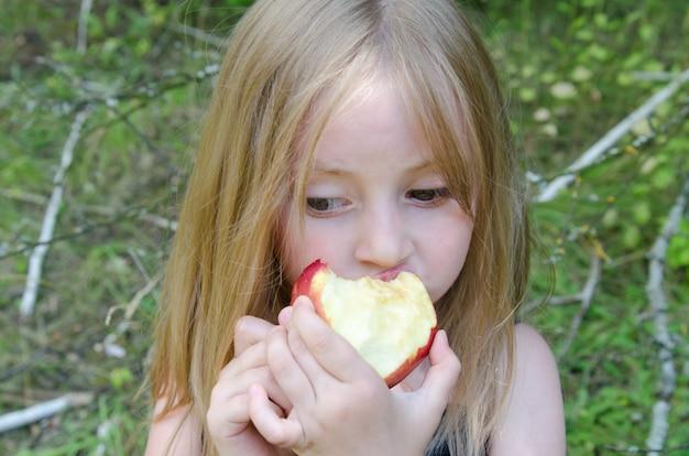 Portrait, petite fille, pré, été, à, décorations, de, fleurs champs, manger, a, pomme Photo Premium