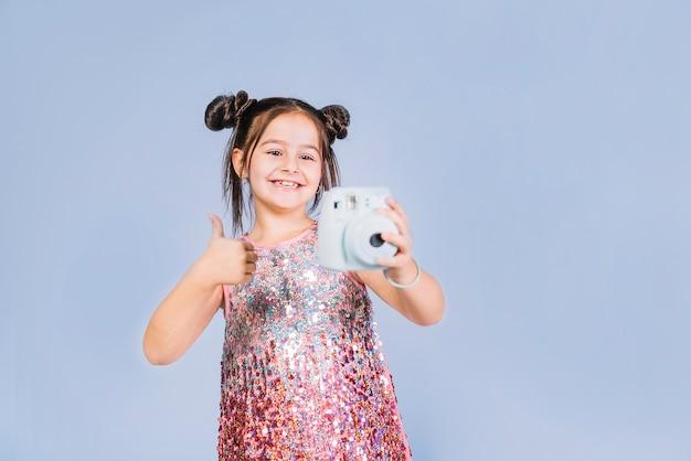 Portrait d'une petite fille tenant une caméra instantanée montrant le pouce en haut Photo gratuit
