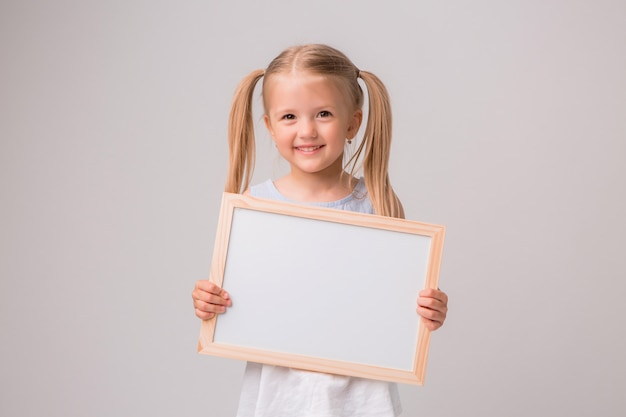 Portrait de petite fille tenant une planche à dessin blanche sur fond blanc Photo Premium