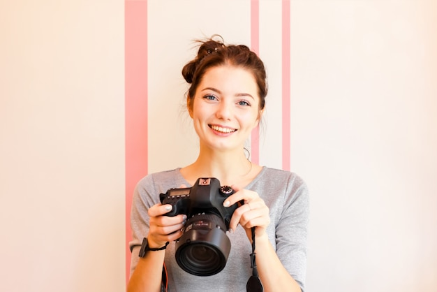 Portrait de photographe fille souriant et tenant son appareil photo Photo Premium
