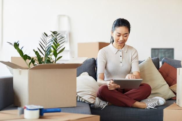 Portrait En Pied De Femme Asiatique Moderne à L'aide De Tablette Numérique Lors Du Déballage Des Boîtes Dans Une Nouvelle Maison Ou Un Appartement Photo Premium