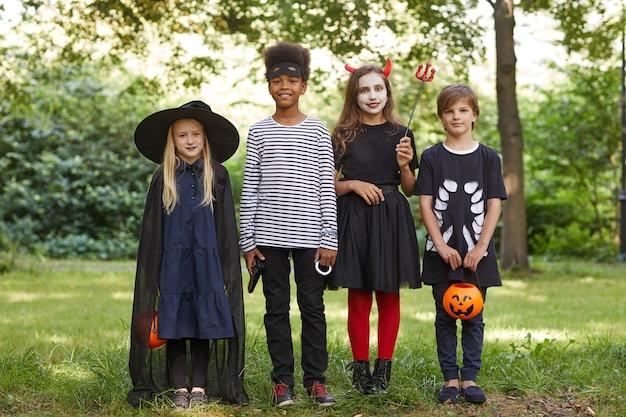 Portrait En Pied D'un Groupe Multiethnique D'enfants Portant Des Costumes D'halloween Debout à L'extérieur Et Photo Premium
